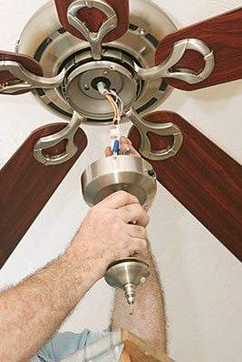 Ceiling fan electrician in chicago il all suburban electric ceil fan being hung up by a man aloadofball Choice Image